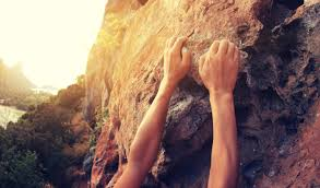 rock climber reaches for a cliff Knowledge Innovation Center